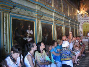 Поки гід тихенько розповідає про церкву та її історію, туристи сидять уздовж стін.